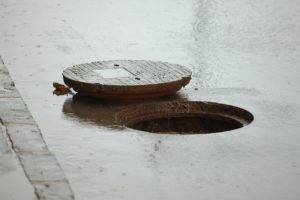 Sewer cover open on a rainy street